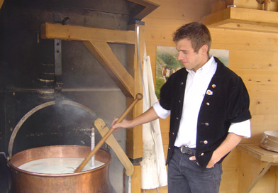 L'Eetivaz cheese being made in the traditonal way, in a copper cauldron over an open wood fire